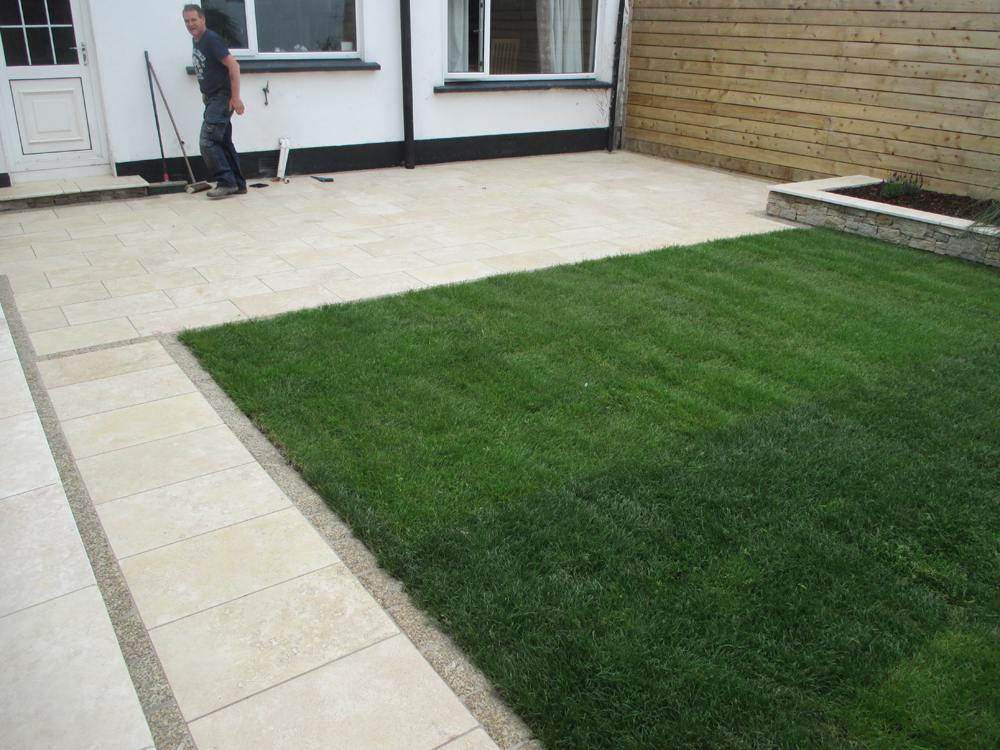 Travertine paving with Granite walls and roll on grass.