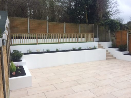 Porcelain paving and steps with walls and artificial grass.