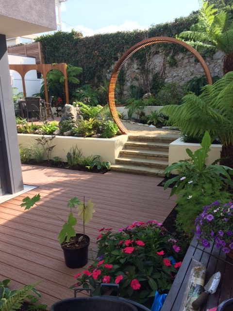 limestone paving and steps with composite Decking and water feature
