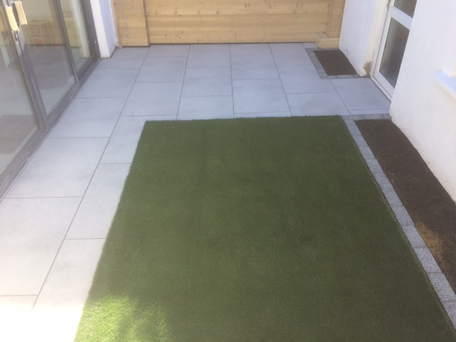 Porcelain slabs with Artificial grass a Timber fence and bench.