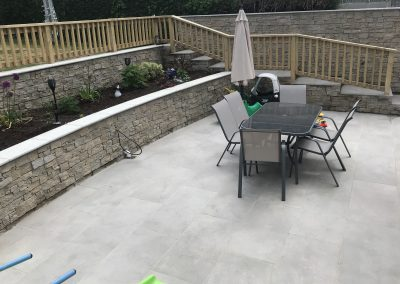 Porcelain Patio with Granite Cladding wall and steps.